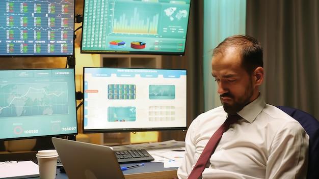 スーツとネクタイを身に着けているビジネスマンは、株式市場の暴落をチェックするラップトップに取り組んでいます。