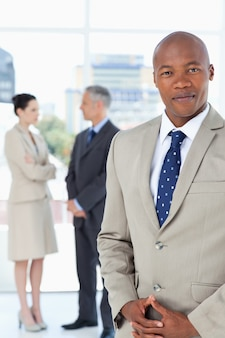 Businessman wearing a suit and crossing his hands with his team behind him