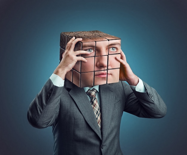 Businessman wearing in suit holding his rubik cube head