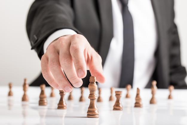 Businessman wearing suit playing chess reaching dark king piece
