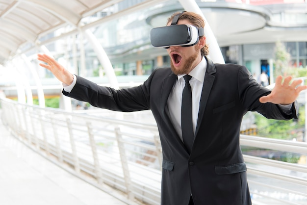 Businessman wearing virtual reality goggle glasses and enjoying in this activity