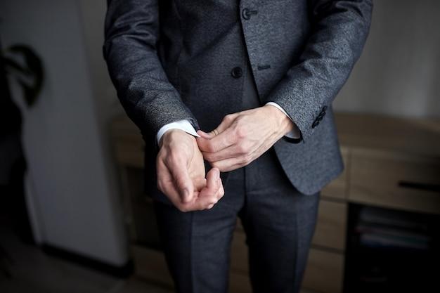 Бизнесмен носит пиджак, мужские руки крупным планом, жених готовится утром перед свадебной церемонией