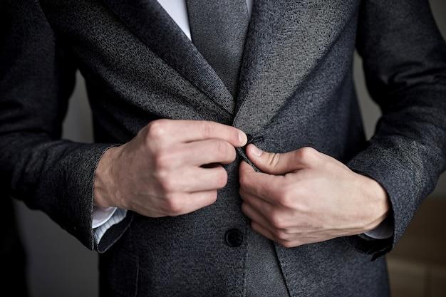 ビジネスマンはジャケットを着て、男性の手のクローズアップ、新郎は結婚式の前に朝の準備をしています