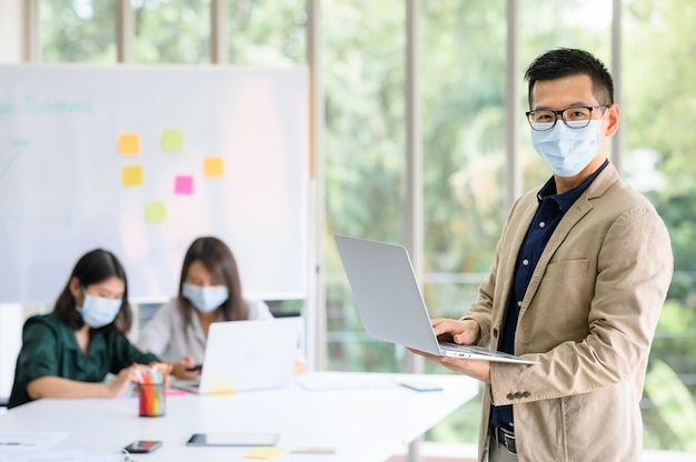 Businessman wears face mask standing and holding laptop with confident