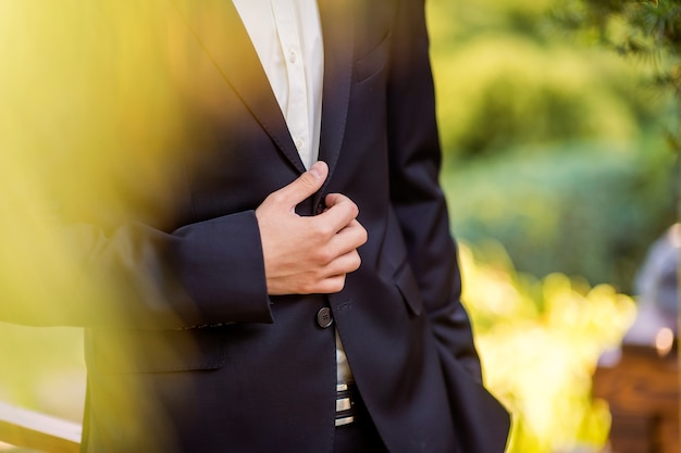 Businessman wears a jacket,male hands closeup,groom getting ready in the morning before wedding ceremony. closeup.