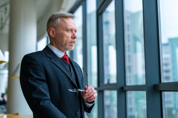 Businessman wears neatly drak suit. holding spectacles in hands. standing near big window with city view looking away.
