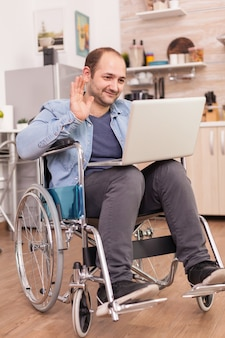 Businessman in wheelchair waving during a video conference on laptop in kitchen while is preparing food. disabled paralyzed handicapped man with walking disability integrating after an accident.