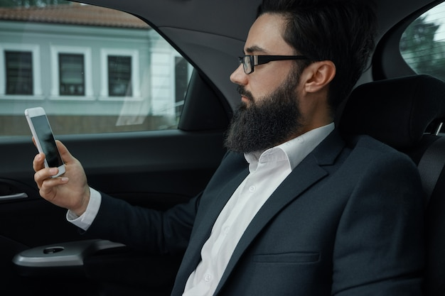A businessman while traveling by car in the back seat using a smartphone