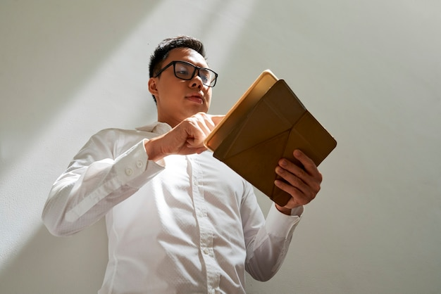 Businessman in white shirt and glasses checking document or email on tablet computer view from below