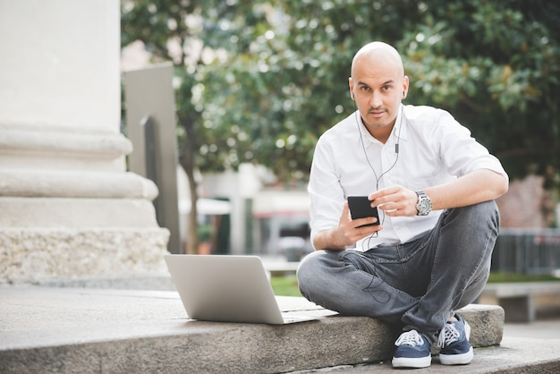 Businessman in white shirt working with laptop sitting on staircase