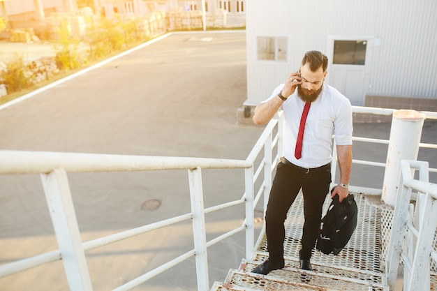 Businessman on white stairs talking on the phone