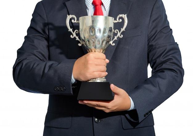ビジネスマン、白い背景にトロフィーを持っているスーツと勝者