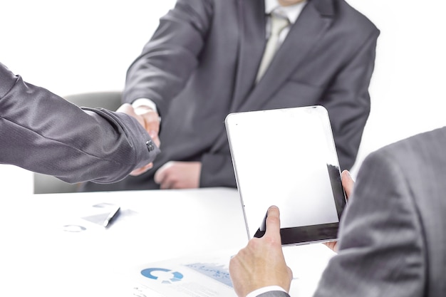 비즈니스 파트너의 악수를 배경으로 디지털 태블릿을 사용하는 사업가
