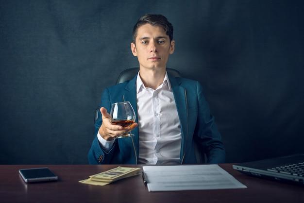 机に座ってワインのグラスを持ったビジネスマン