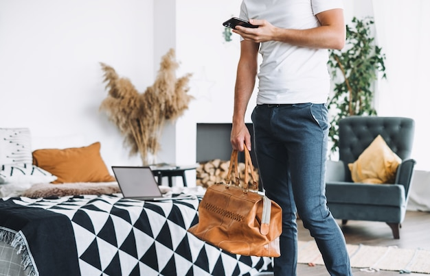 彼の手に電話とベッドの近くに自宅で旅行バッグを持って出張に行くビジネスマン