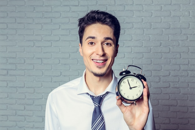 Businessman with an alarm clock in a hand