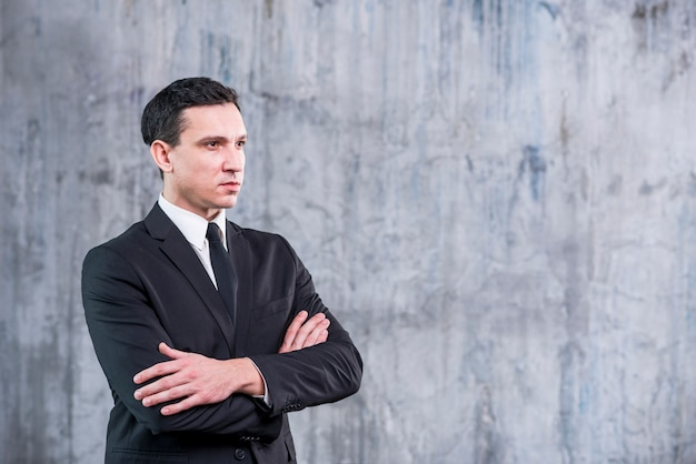 Businessman with arms crossed looking away