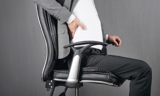 Businessman with back pain sitting in office chair.