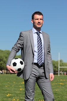 夏の公園でボールを持つビジネスマン