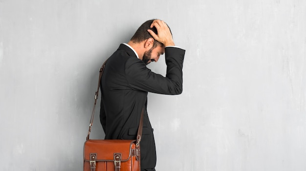 Businessman with beard on back position looking back while scratching head