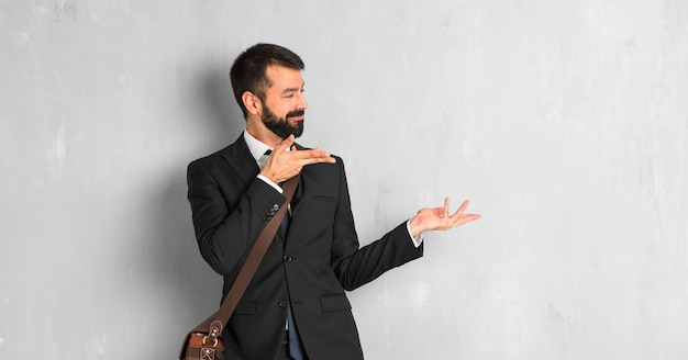 Businessman with beard extending hands to the side for inviting to come