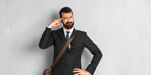 Businessman with beard making the gesture of madness putting finger on the head