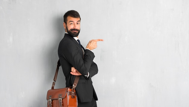 Businessman with beard pointing finger to the side in lateral position