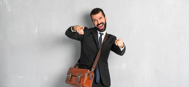 Businessman with beard points finger at you while smiling