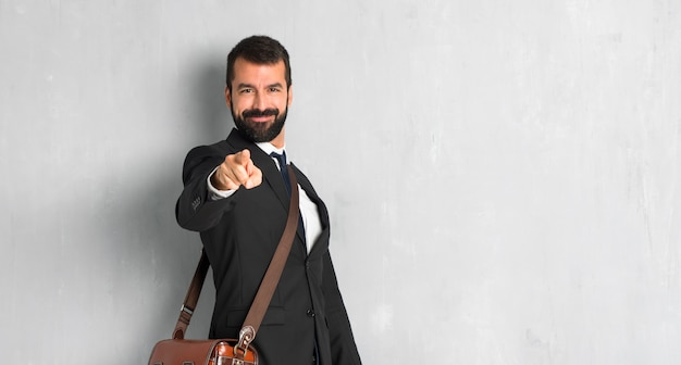 Businessman with beard points finger at you with a confident expression