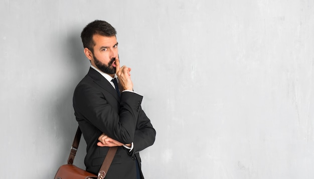 Businessman with beard showing a sign of closing mouth and silence gesture