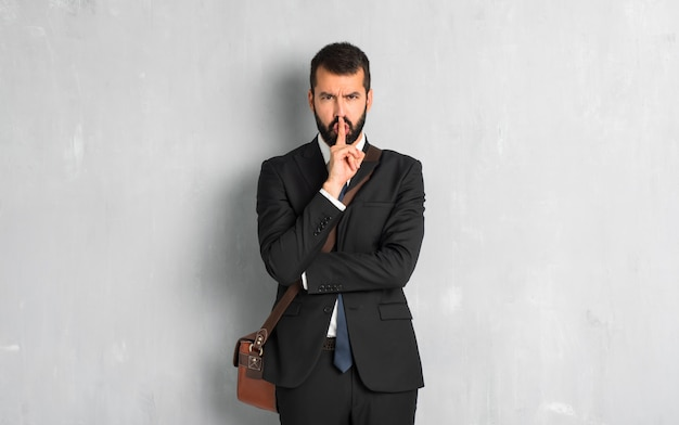 Businessman with beard showing a sign of silence gesture putting finger in mouth