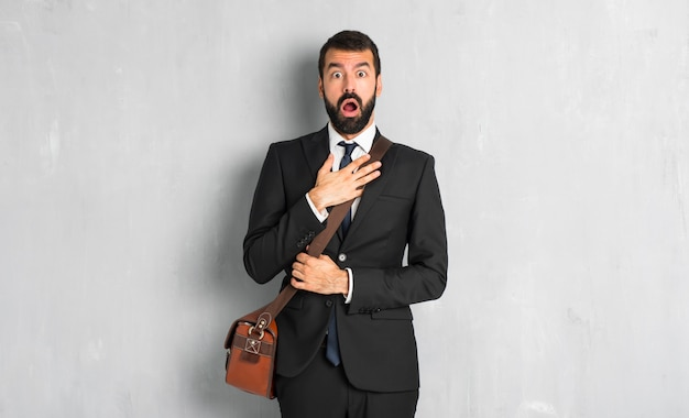 Businessman with beard surprised and shocked while looking right