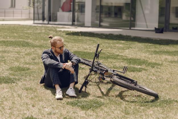 夏の街で自転車を持ったビジネスマン