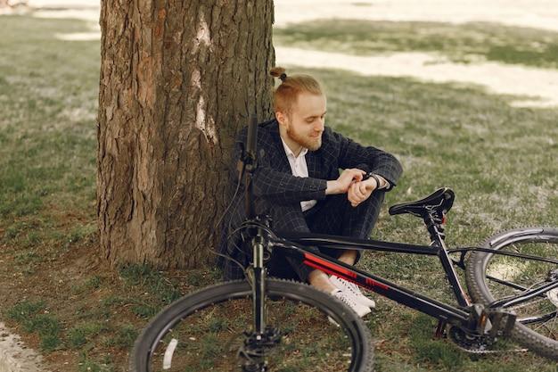 Бизнесмен с велосипедом в летнем городе