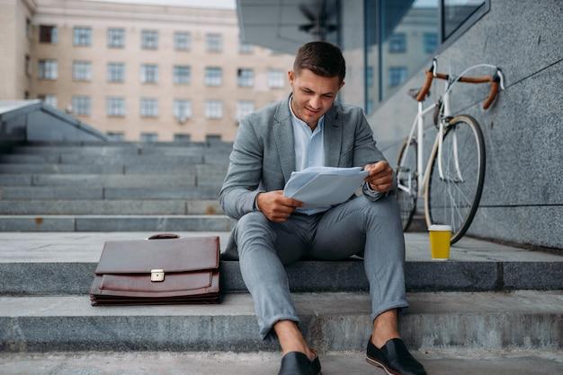 자전거와 서류 가방 사무실 시내에서 건물에서 점심을 먹고 사업가.