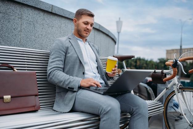自転車を持っているビジネスマンは、ダウンタウンのオフィスビルのベンチでコーヒーを飲みます。街の通り、都会的なスタイルでエコ輸送に乗るビジネスパーソン