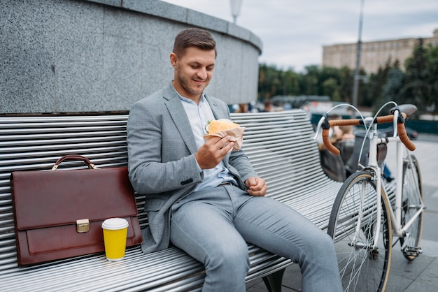 Businessman with bike eats lunch on the bench at the office building in downtown.