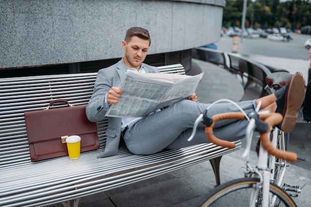 Businessman with bike reading newspaper on the bench at the office building in downtown.