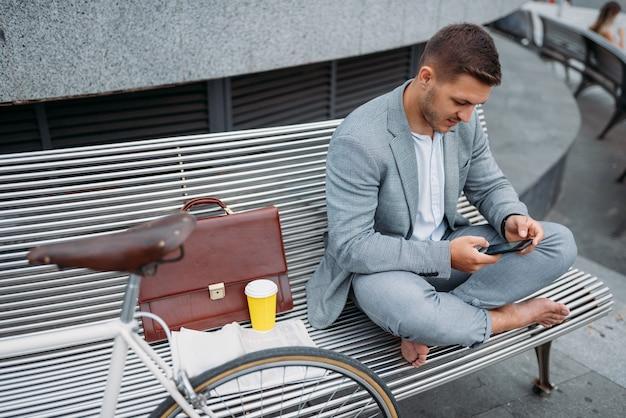 Бизнесмен с велосипедом, отдыхая на скамейке в офисном здании в центре города.
