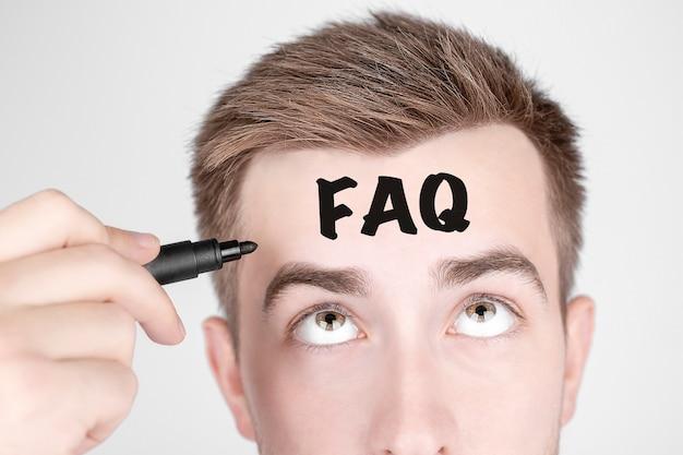 Бизнесмен с черным маркером пишет слово faq на лбу