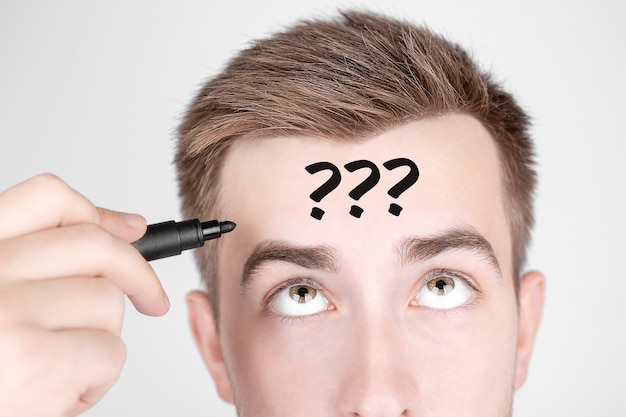 Businessman with black marker writes the word questions on his forehead