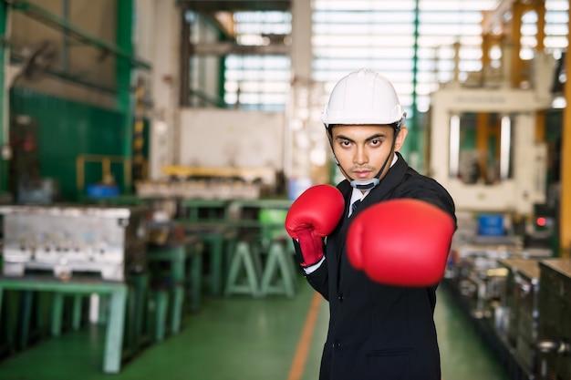 黒のスーツと赤いボクシンググローブのヘルメットを持つビジネスマンは、covid19の間に工場危機のために戦う