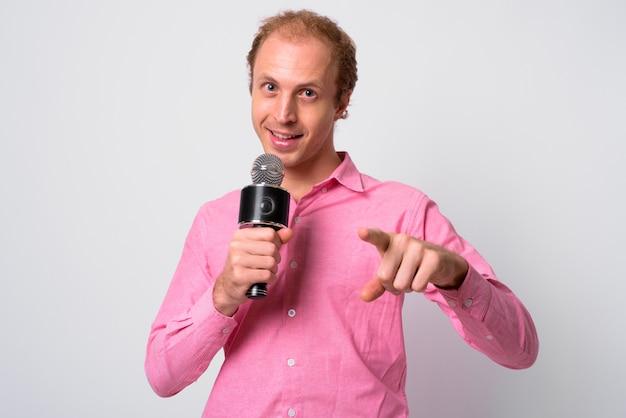 흰 벽에 분홍색 셔츠를 입고 금발 머리를 가진 사업가