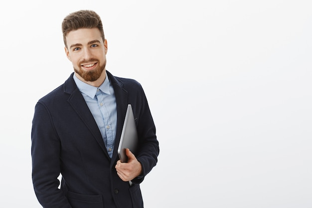 Businessman with blue eyes and beard standing self-assured in formal suit holding laptop in hand gazing pleased and assured, being ambitious and successful