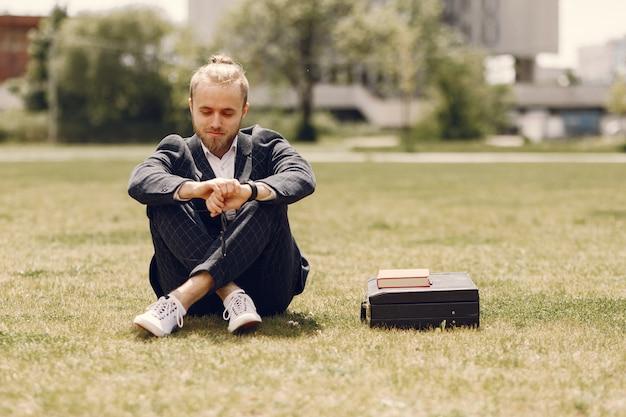 夏の街に座って本を持ったビジネスマン