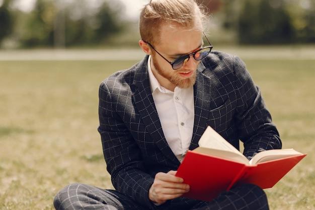 Бизнесмен с книгой, сидя в летнем городе