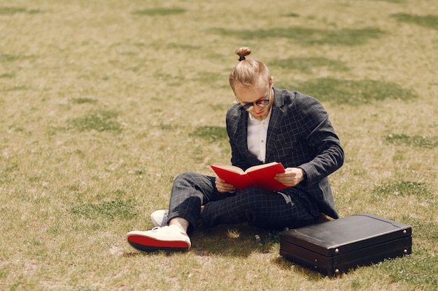 Businessman with book sitting in a summer city