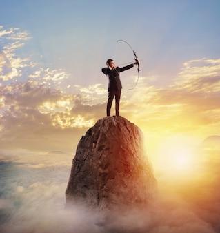 山の頂上に弓を持つビジネスマン