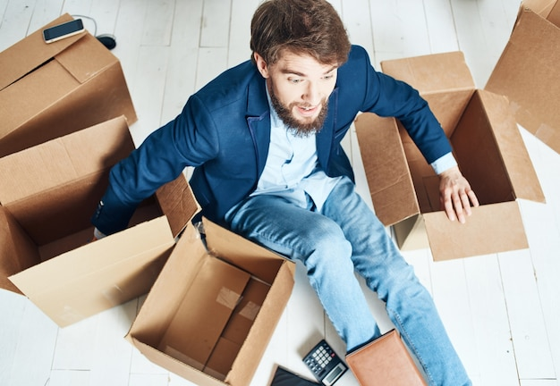 Бизнесмен с коробками сидит в офисе