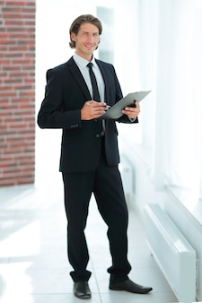 Businessman with business document standing in office